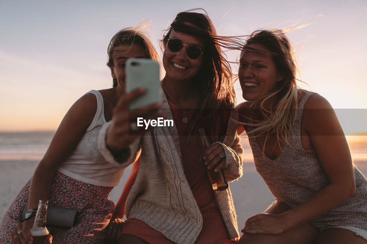 wireless technology, water, sky, technology, leisure activity, beach, communication, sea, photography themes, togetherness, real people, lifestyles, nature, mobile phone, land, holding, young adult, young women, friendship, smiling, fashion, outdoors