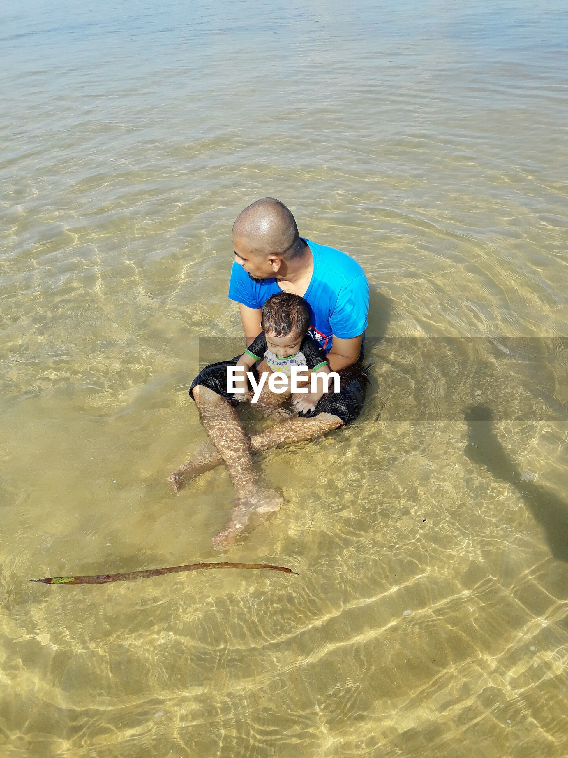 High angle view of father holding cute son while sitting on shore at beach