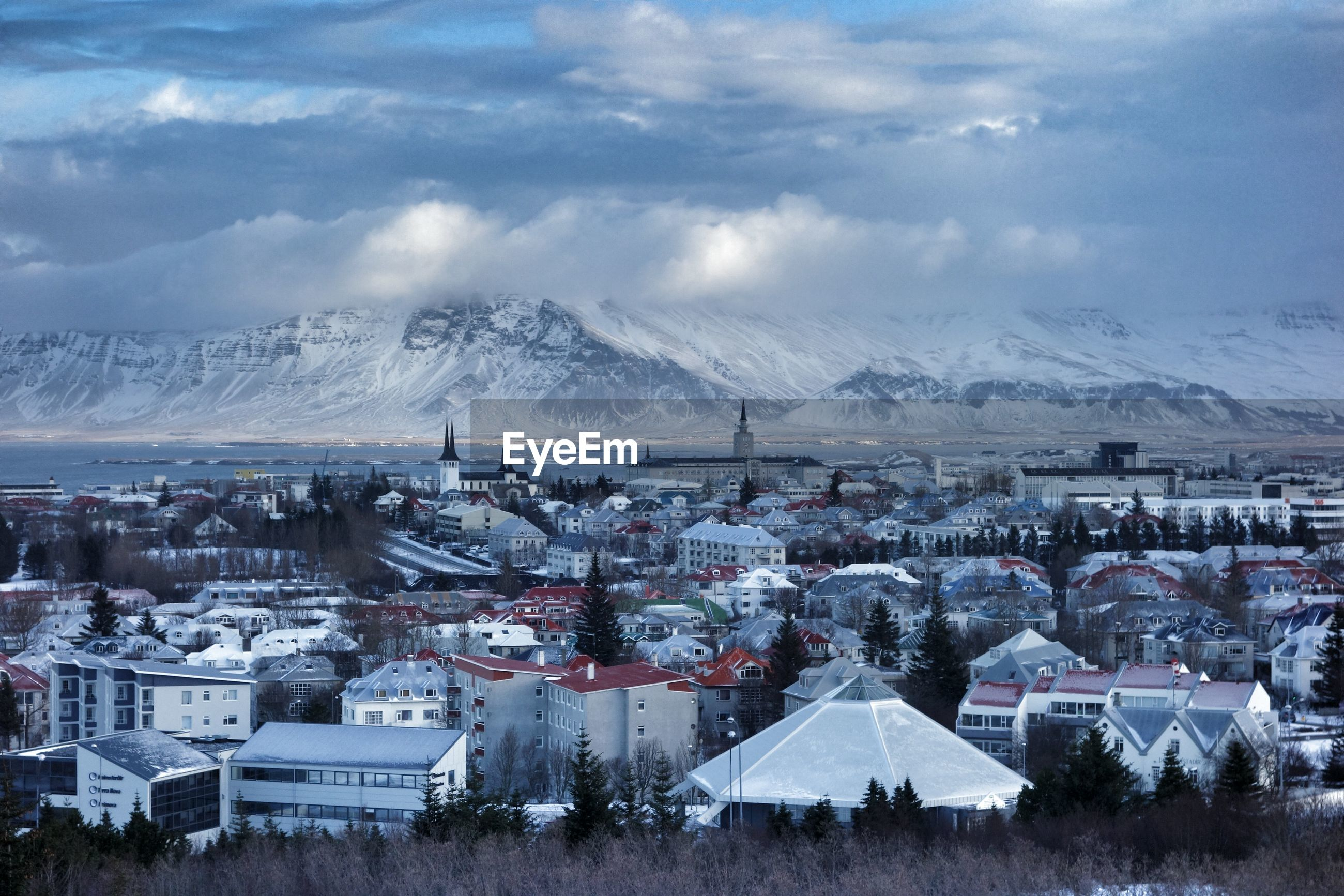 Buildings and snowcapped mountains against cloudy sky