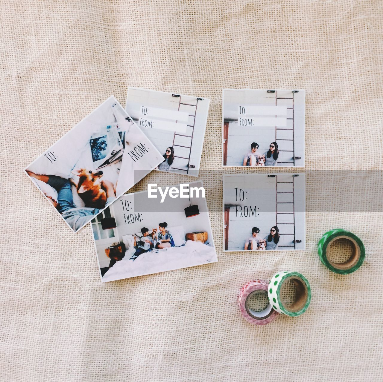 High Angle View Of Photographs And Adhesive Tapes On Burlap