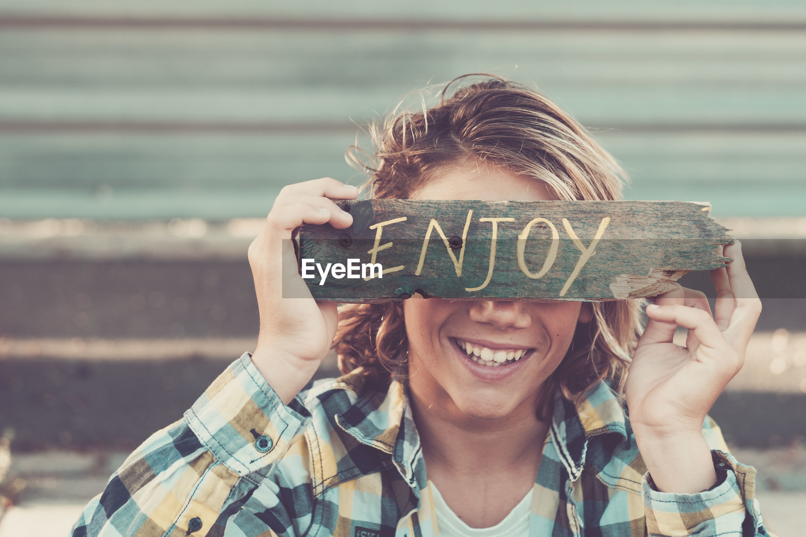 Close-up of smiling teenage boy holding wood with text