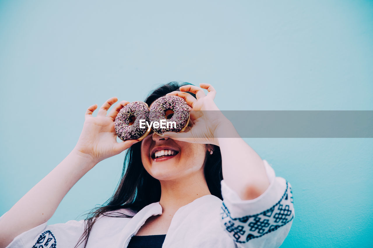 Low Angle View Of Smiling Young Woman Holding Donuts Against Clear Blue Sky