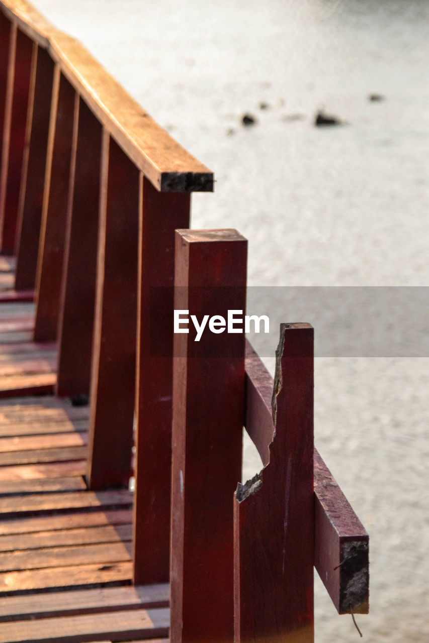 wood - material, no people, in a row, focus on foreground, day, water, architecture, nature, built structure, beach, outdoors, sea, selective focus, brown, land, railing, tranquility, wood, staircase, wooden post