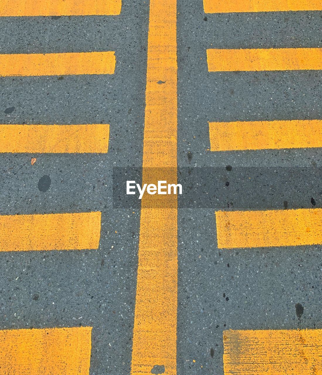 road, symbol, transportation, road marking, sign, yellow, asphalt, marking, high angle view, no people, backgrounds, city, direction, day, striped, guidance, street, full frame, safety, pattern, outdoors, dividing line, parallel