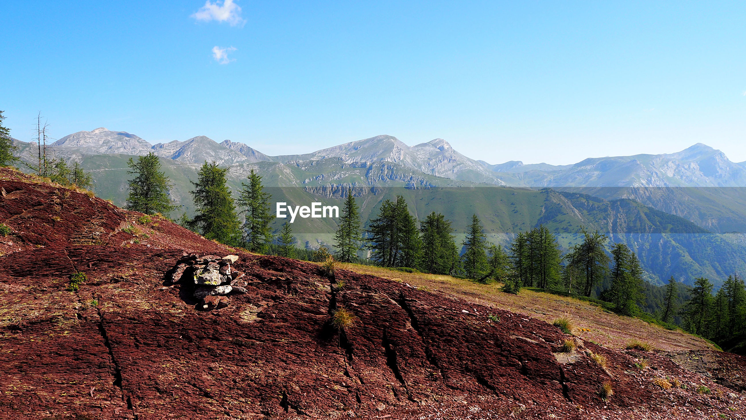 Scenic view of red land and  mountains against clear blue sky