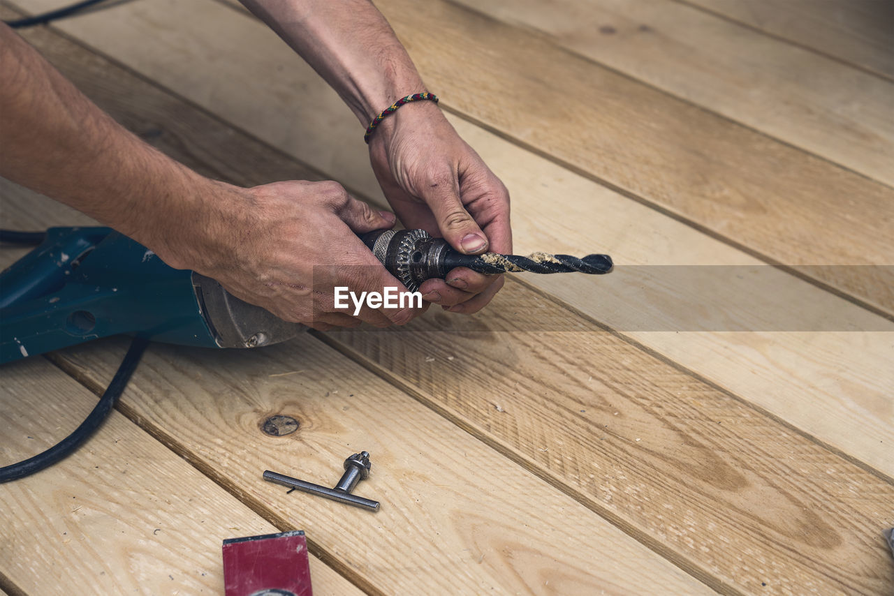HIGH ANGLE VIEW OF MAN WORKING ON WOOD TABLE