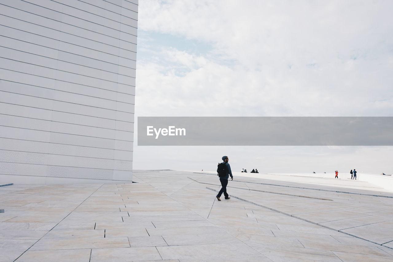 Man Walking On Walkway At Oslo Opera House Against Sky