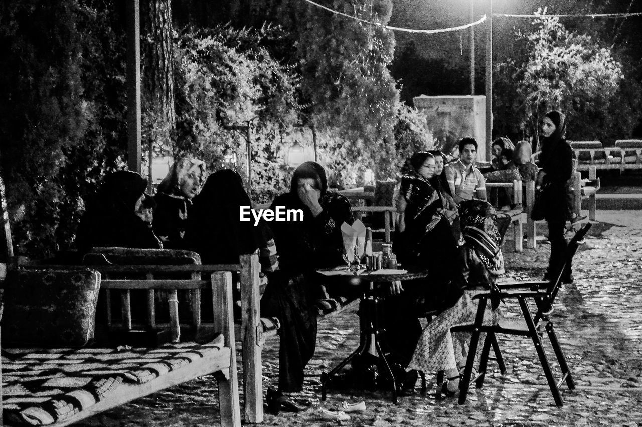 full length, real people, chair, table, sitting, leisure activity, togetherness, lifestyles, night, outdoors, women, tree, men, young adult, friendship, people, adult, adults only