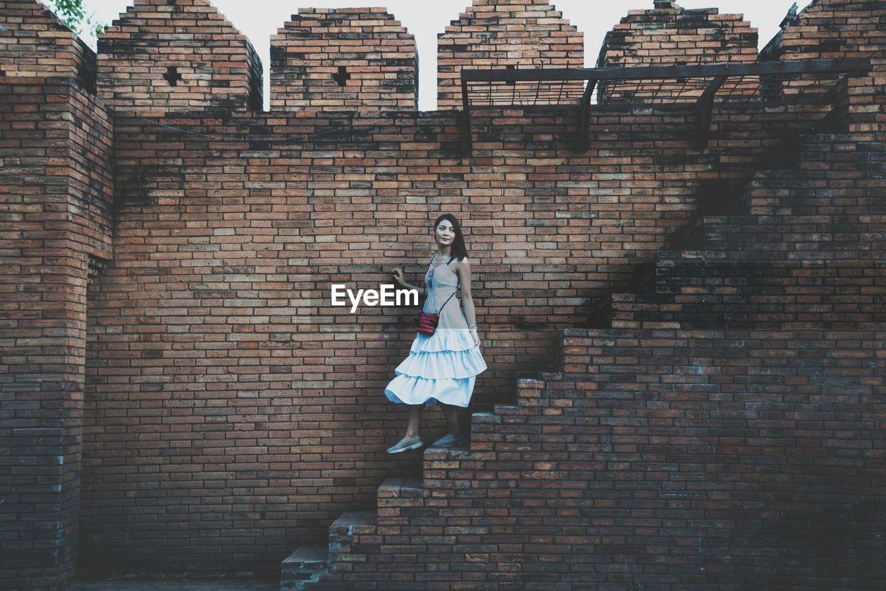 Woman walking on steps by brick wall
