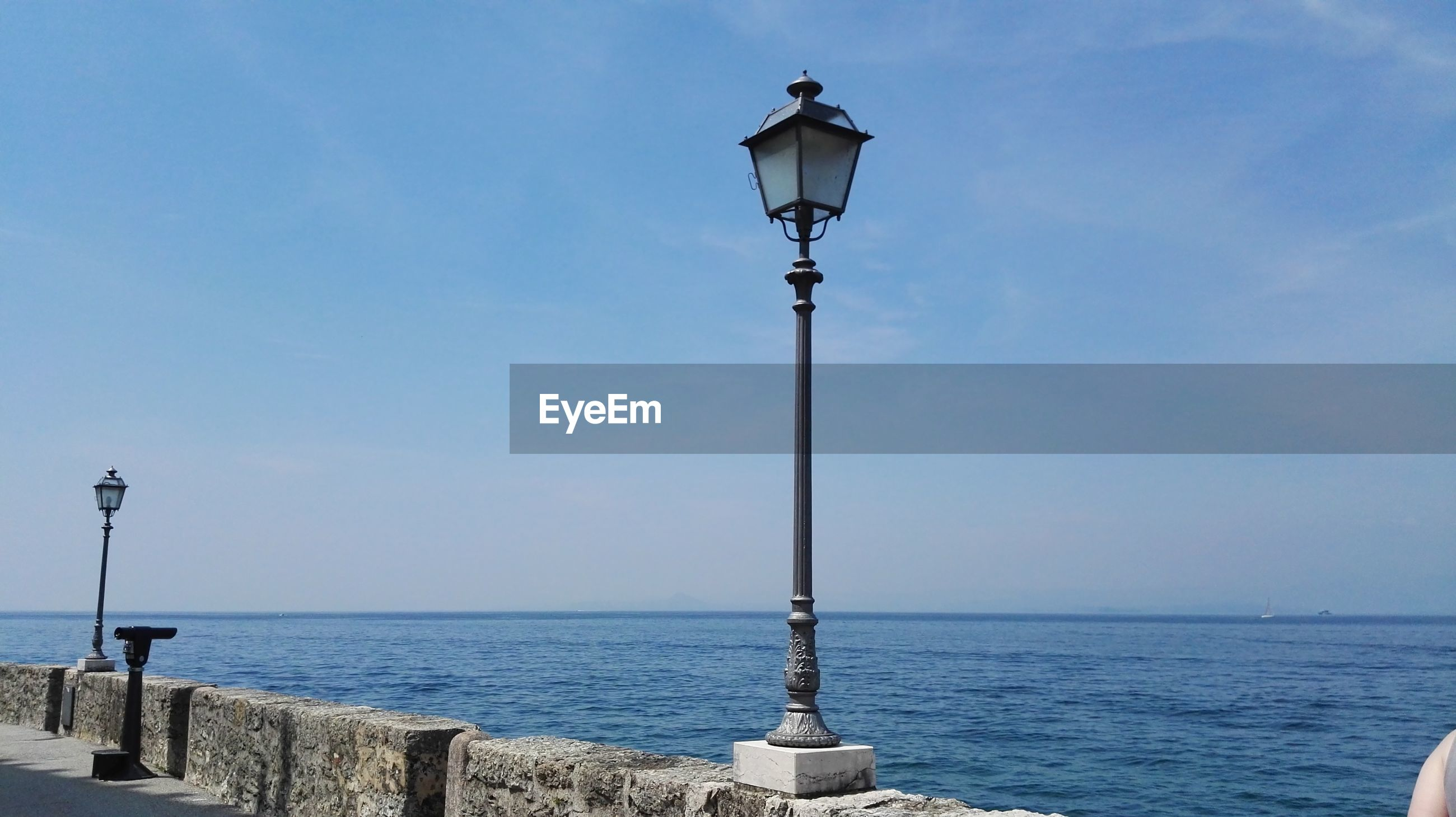 sea, street light, lighting equipment, water, horizon over water, scenics, nature, tranquility, beauty in nature, gas light, tranquil scene, outdoors, day, sky, no people, blue, clear sky, perching