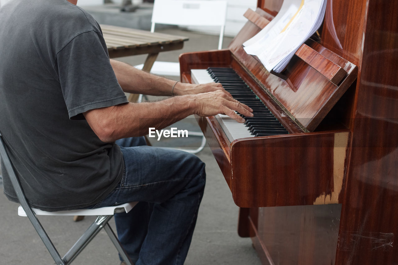 Midsection Of Man Playing Piano