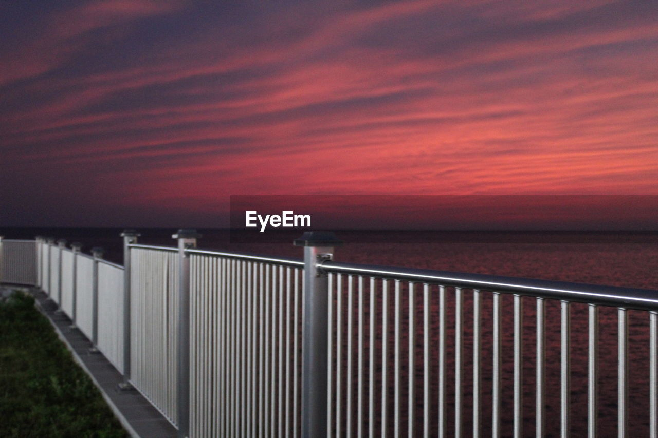 sky, sea, cloud - sky, railing, water, horizon over water, sunset, beauty in nature, horizon, scenics - nature, nature, tranquil scene, tranquility, no people, built structure, architecture, barrier, outdoors, beach