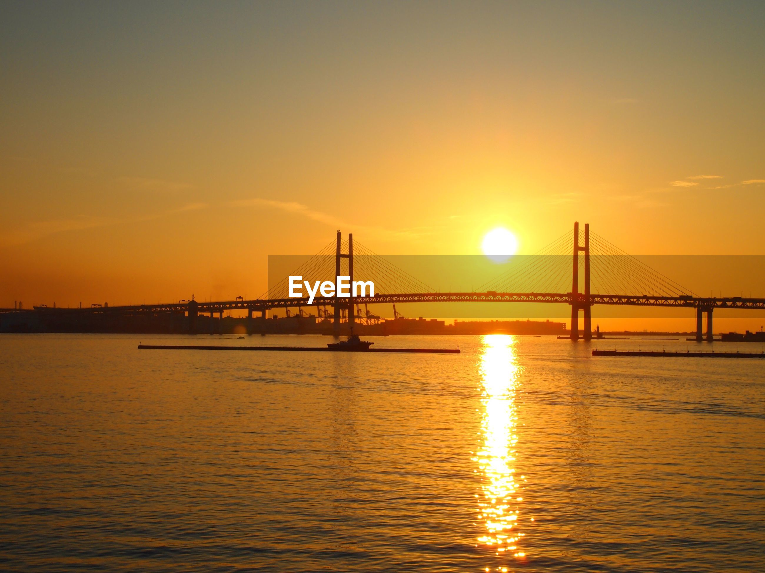 SCENIC VIEW OF BRIDGE OVER SEA AGAINST SKY DURING SUNSET