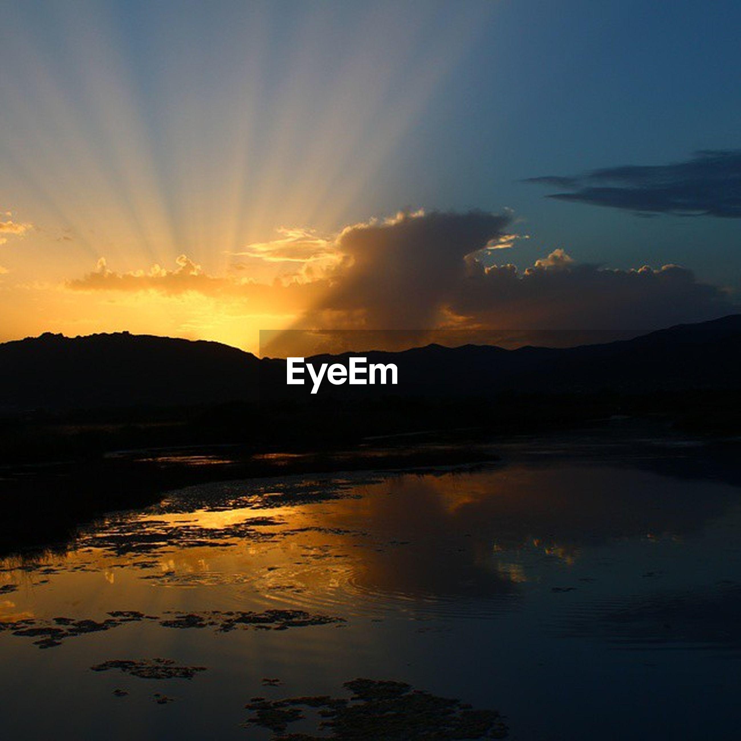 sunset, water, tranquil scene, scenics, reflection, tranquility, beauty in nature, silhouette, lake, sky, mountain, idyllic, nature, orange color, sun, cloud - sky, calm, majestic, sunlight, non-urban scene