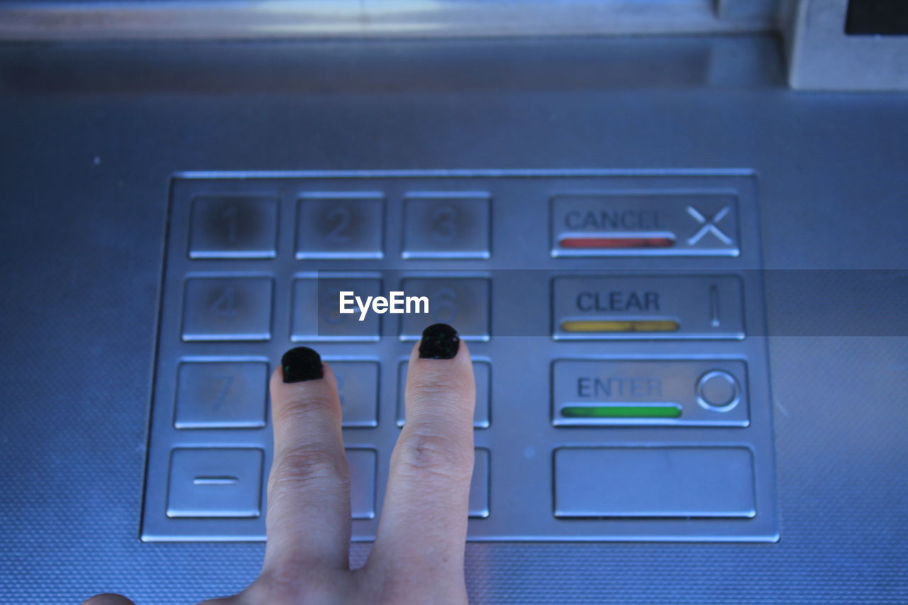 Cropped image of woman operating atm machine