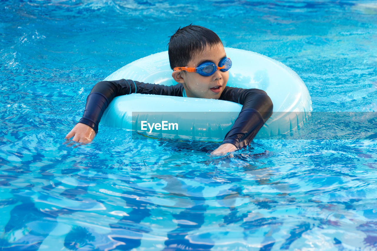 water, one person, lifestyles, pool, swimming pool, swimming, real people, leisure activity, eyewear, swimming goggles, waterfront, blue, swimwear, males, day, nature, sunlight, men, outdoors