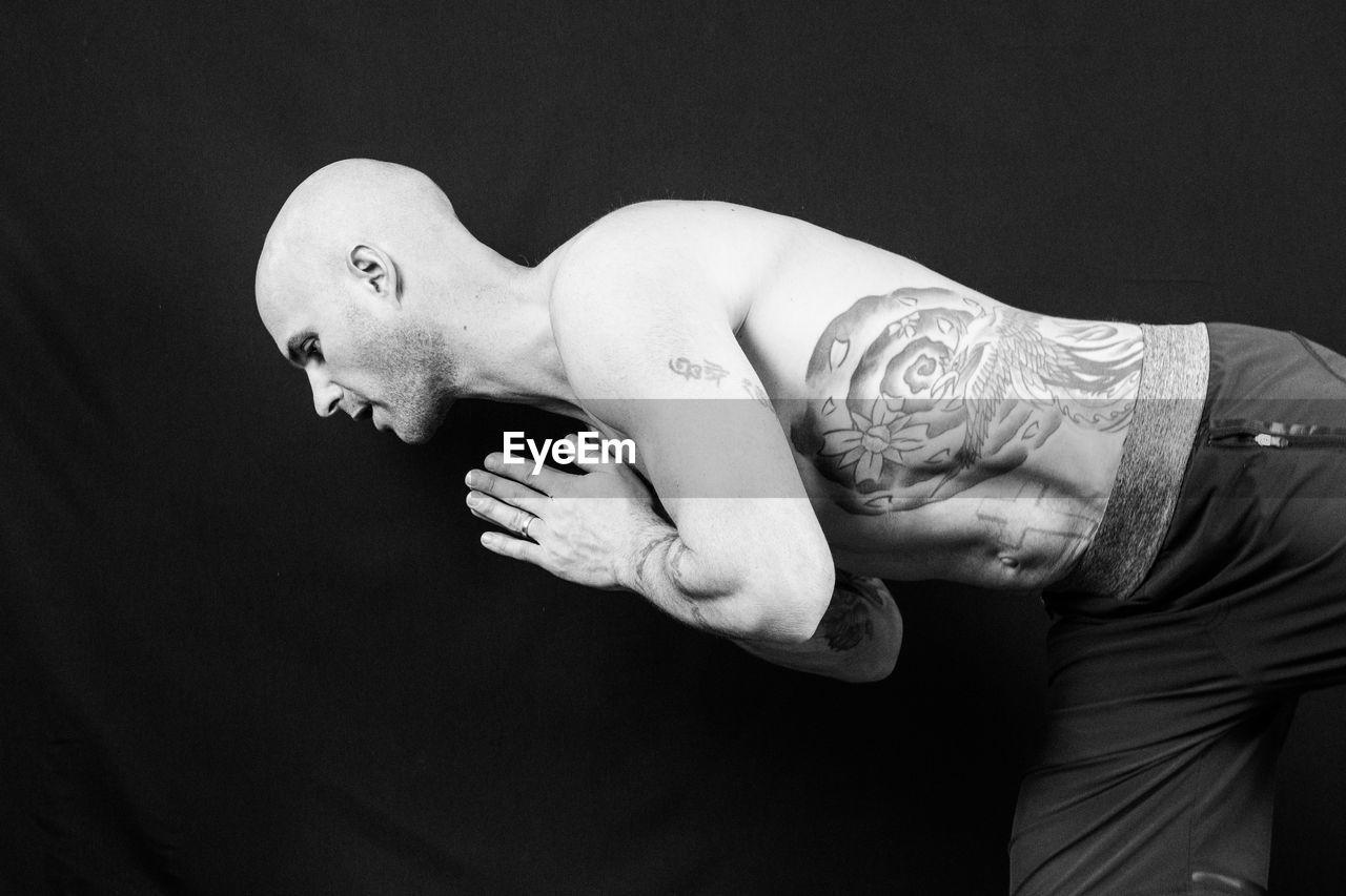 Shirtless Bald Man Doing Yoga Against Black Background