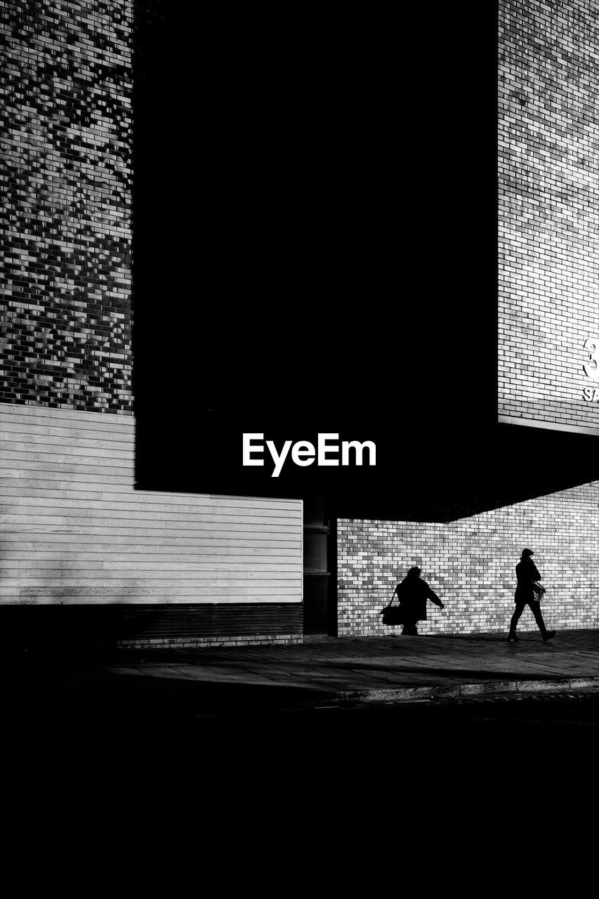 silhouette, architecture, two people, city, building exterior, men, walking, street, day, built structure, full length, people, transportation, adult, nature, real people, outdoors, footpath, road, shadow