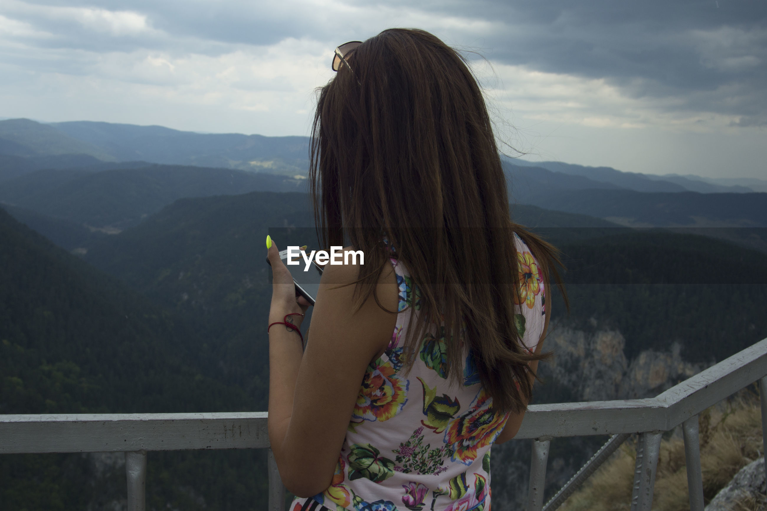 Rear view of woman using mobile phone while standing against mountains