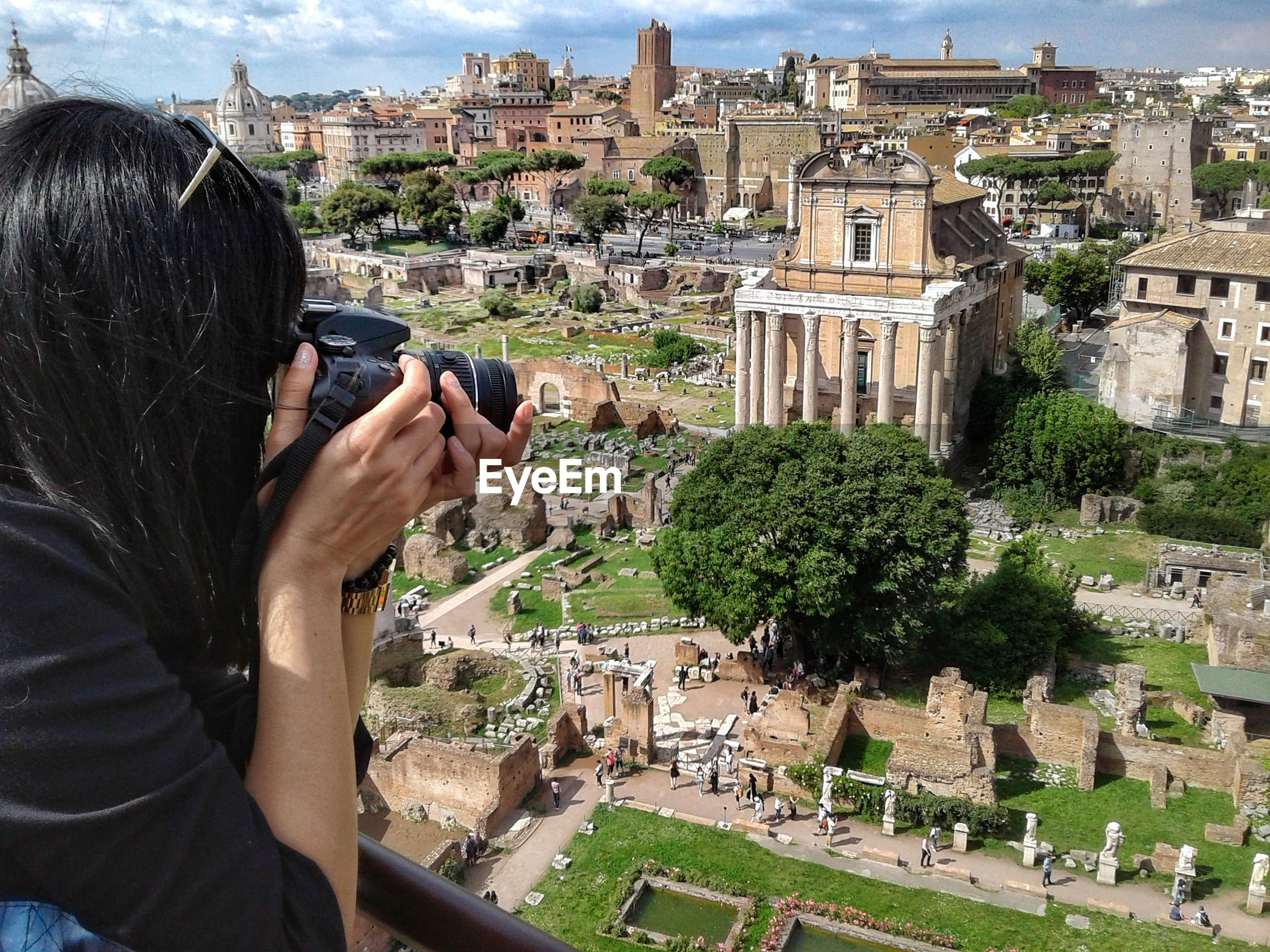 Woman photographing historical buildings in city
