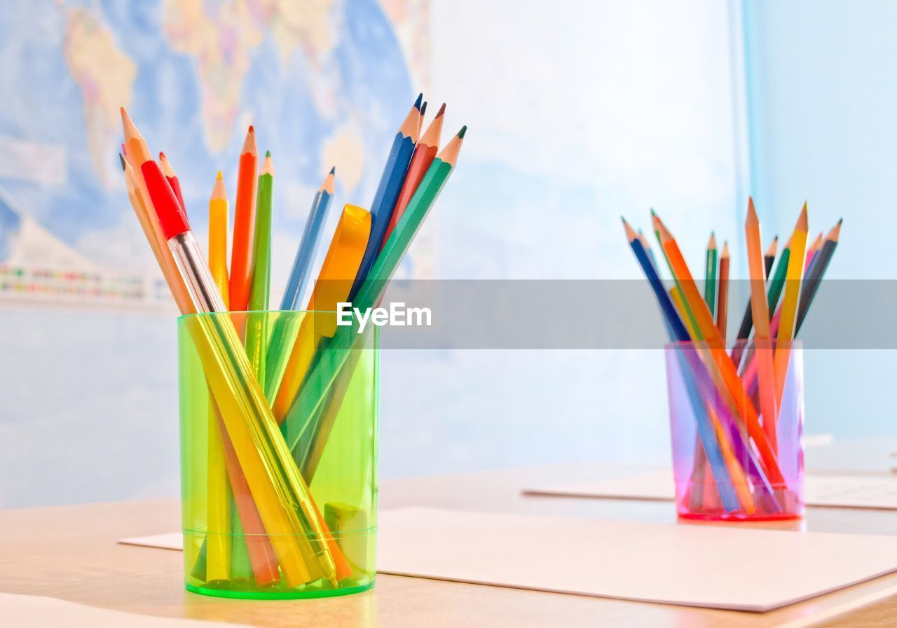 Close-up of multi colored pencils in desk organizers on table