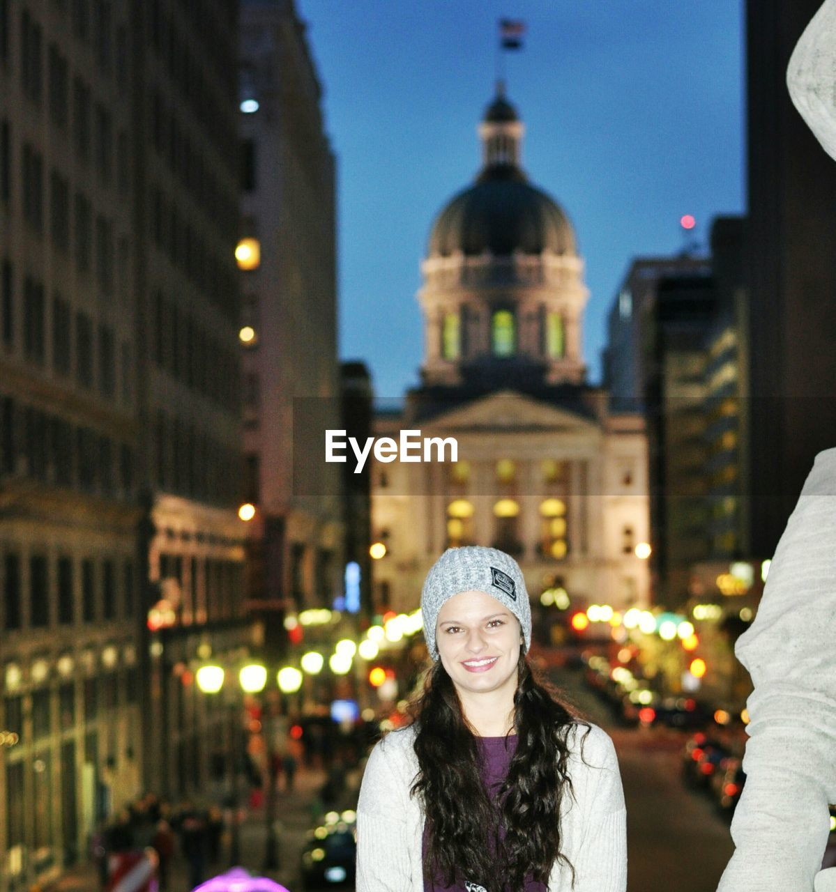 Portrait Of Happy Young Woman Against Indiana State Capitol At Night