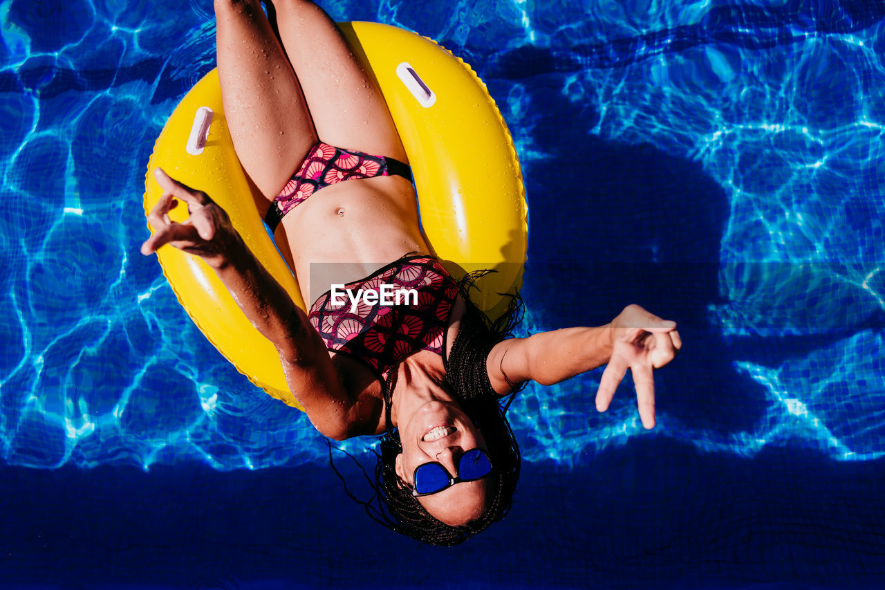 MIDSECTION OF WOMAN IN SWIMMING POOL IN WATER
