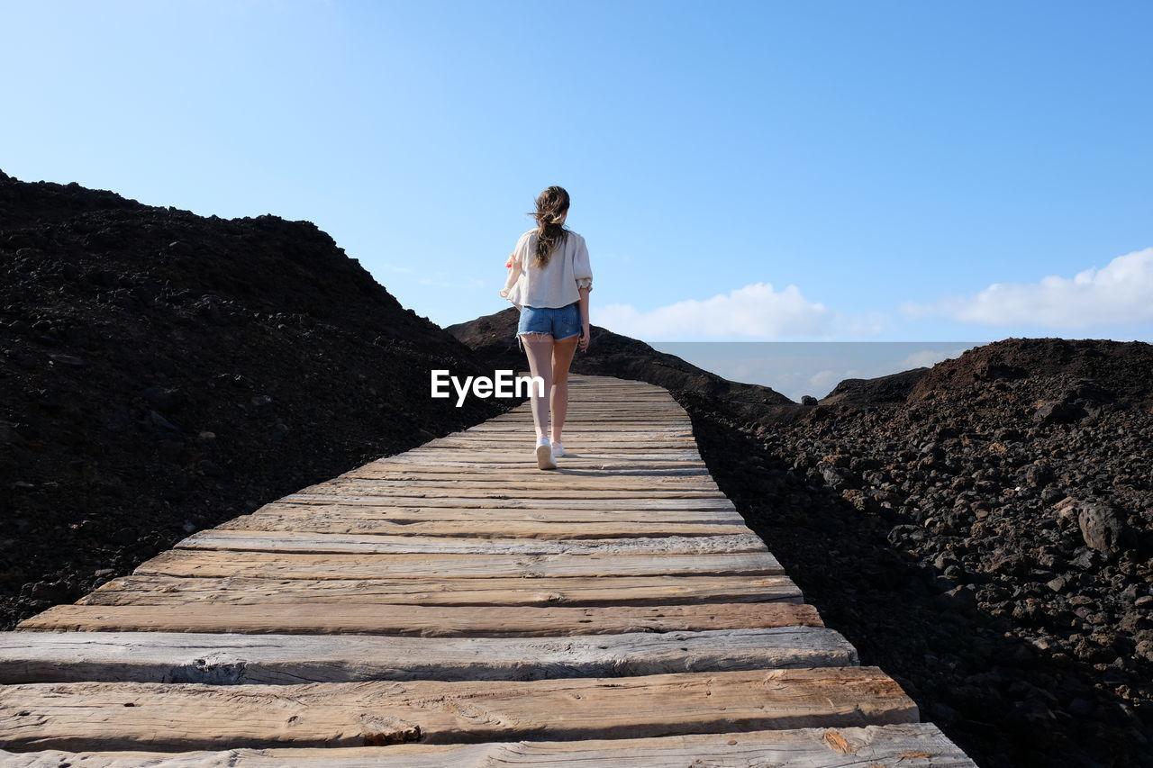 Rear View Of Woman Walking On Boardwalk