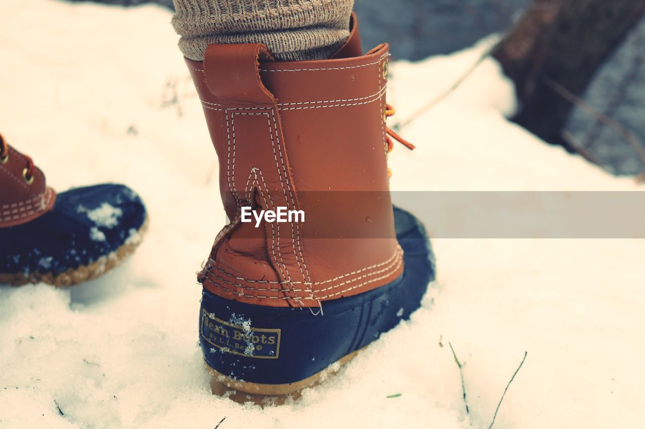one person, shoe, human body part, body part, day, low section, focus on foreground, snow, human leg, winter, land, real people, cold temperature, nature, close-up, outdoors, women, boot, human limb, human foot, personal accessory, warm clothing, jeans