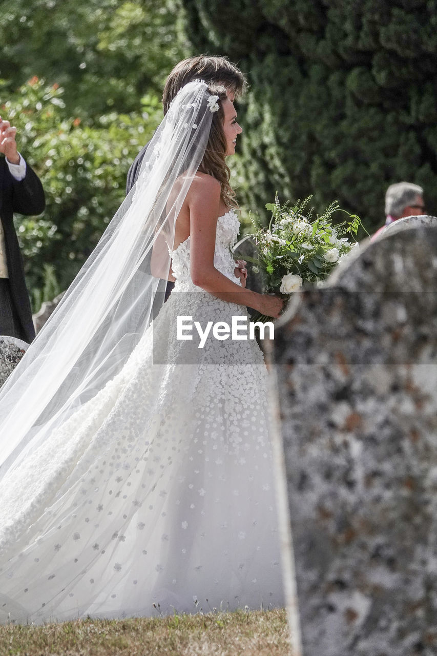 newlywed, wedding, bride, event, wedding dress, women, young adult, life events, celebration, real people, adult, young women, plant, flower, married, standing, side view, people, nature, bouquet, fashion, veil, wife, hair, flower arrangement, outdoors, couple - relationship, beautiful woman, positive emotion
