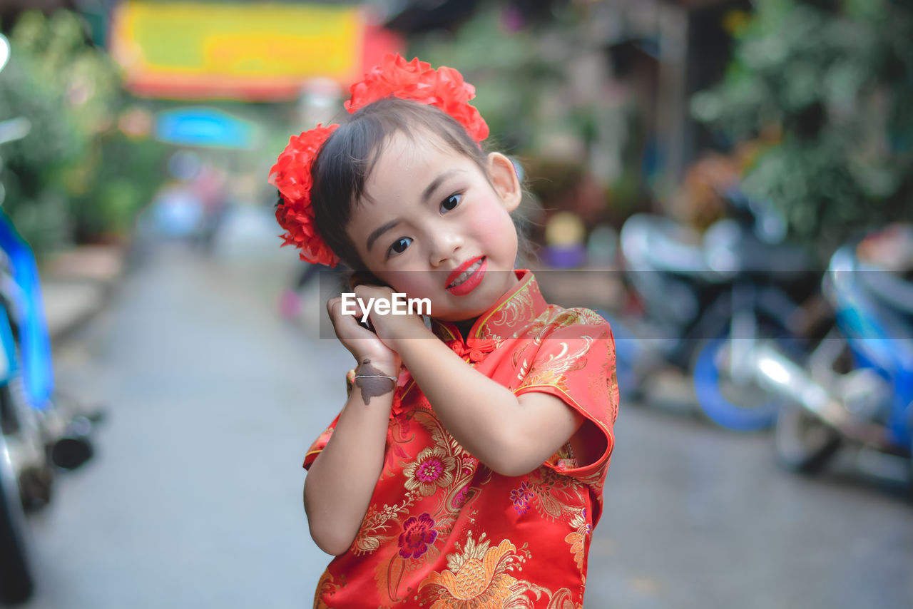 Portrait of cute girl in traditional red clothing standing on street