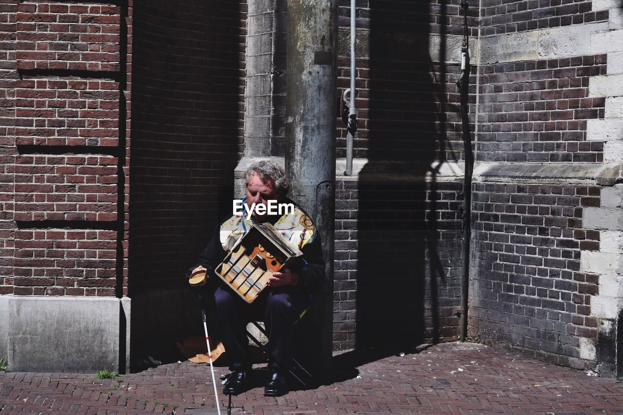 Full Length Of Man Holding Box While Sitting On Chair By Brick Wall