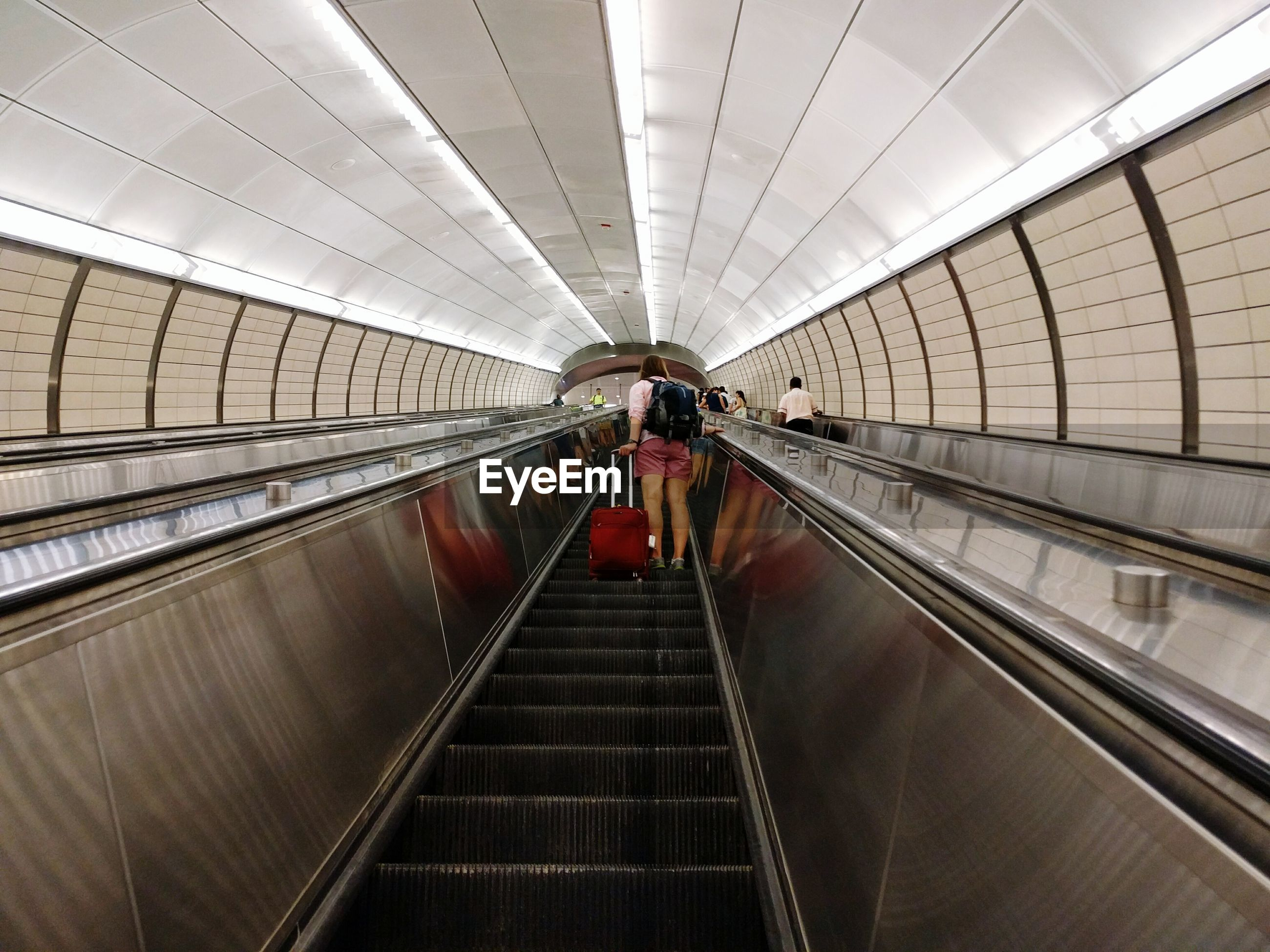 Rear view of woman with luggage standing on escalator in airport