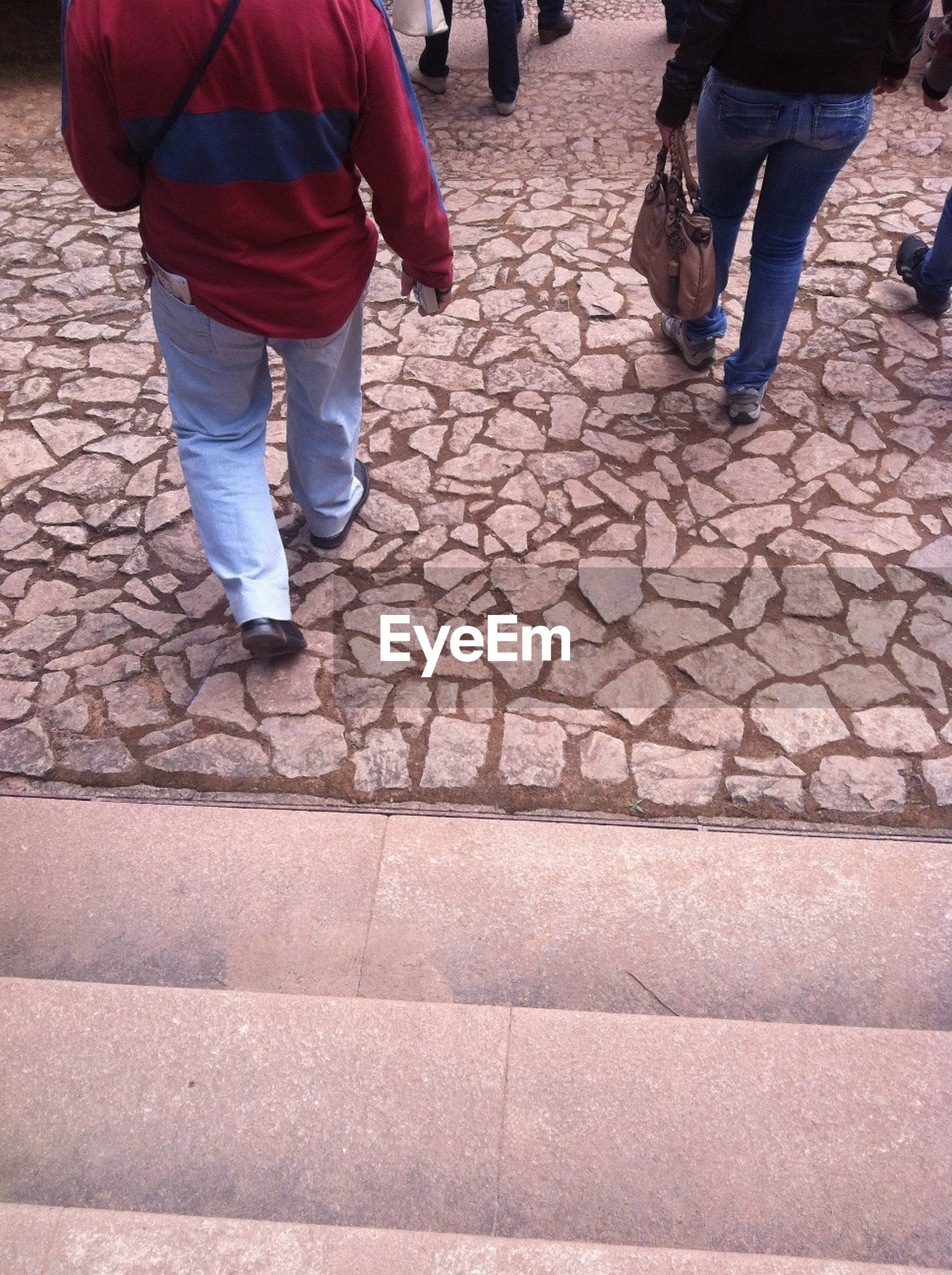low section, person, lifestyles, men, walking, cobblestone, street, leisure activity, standing, paving stone, footpath, sidewalk, casual clothing, the way forward, shoe