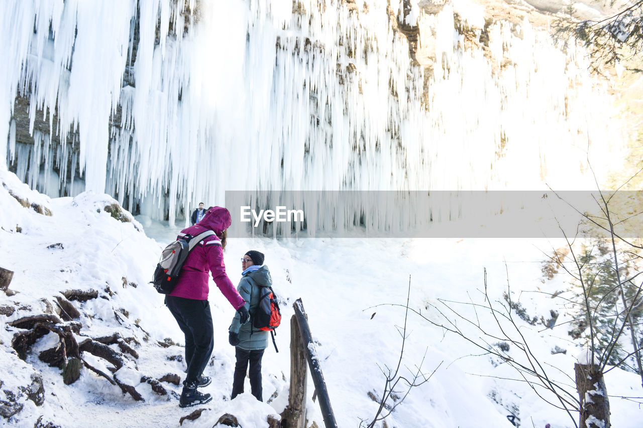winter, cold temperature, snow, nature, weather, two people, real people, beauty in nature, rear view, white color, leisure activity, adventure, lifestyles, outdoors, full length, tranquility, day, warm clothing, scenics, tree, mountain, sky