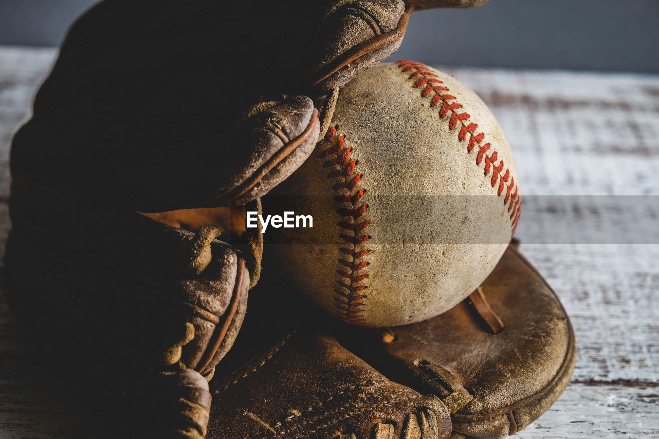 Close-up of baseball gloves and ball on table