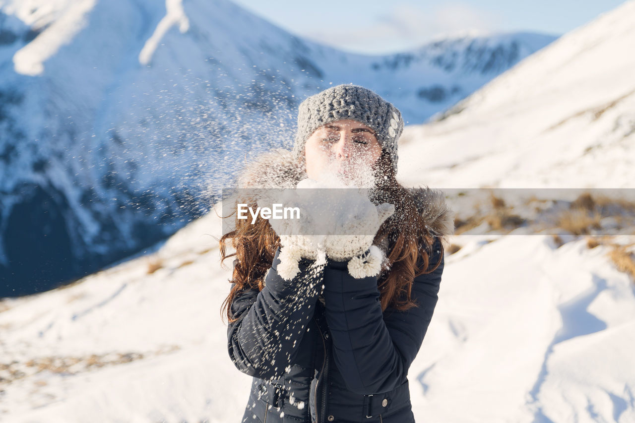 Cheerful Woman Wearing Fur Coat While Standing Against Mountains During Winter