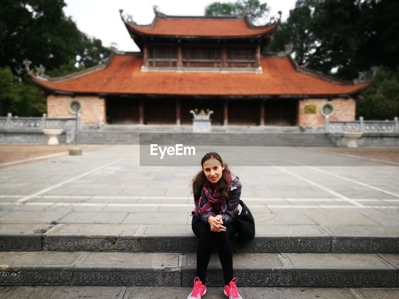 Portrait of smiling woman sitting on steps against building