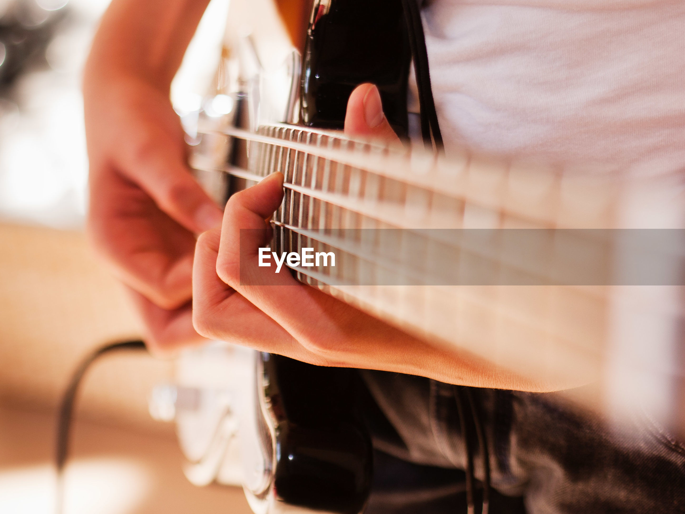 Close-up of person playing electric guitar