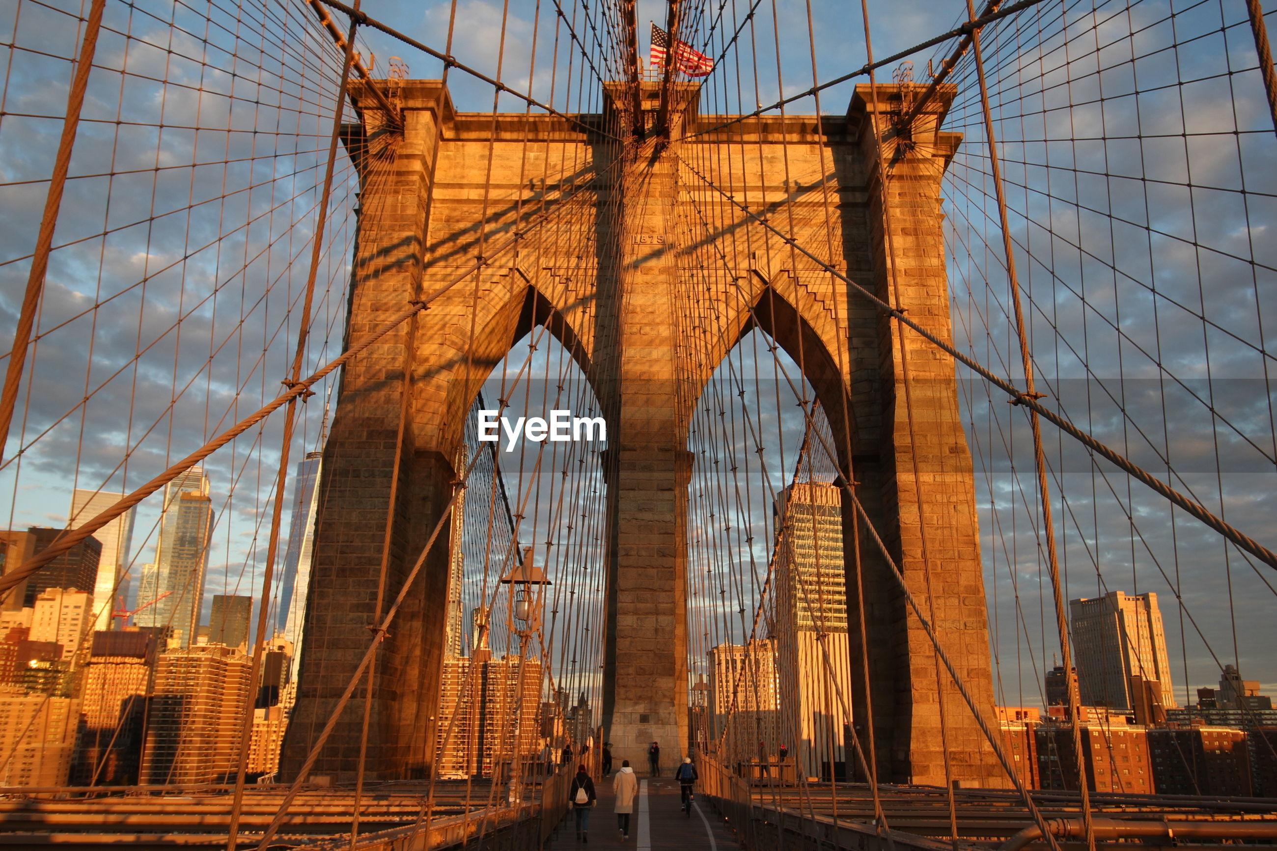LOW ANGLE VIEW OF SUSPENSION BRIDGE AGAINST CITYSCAPE