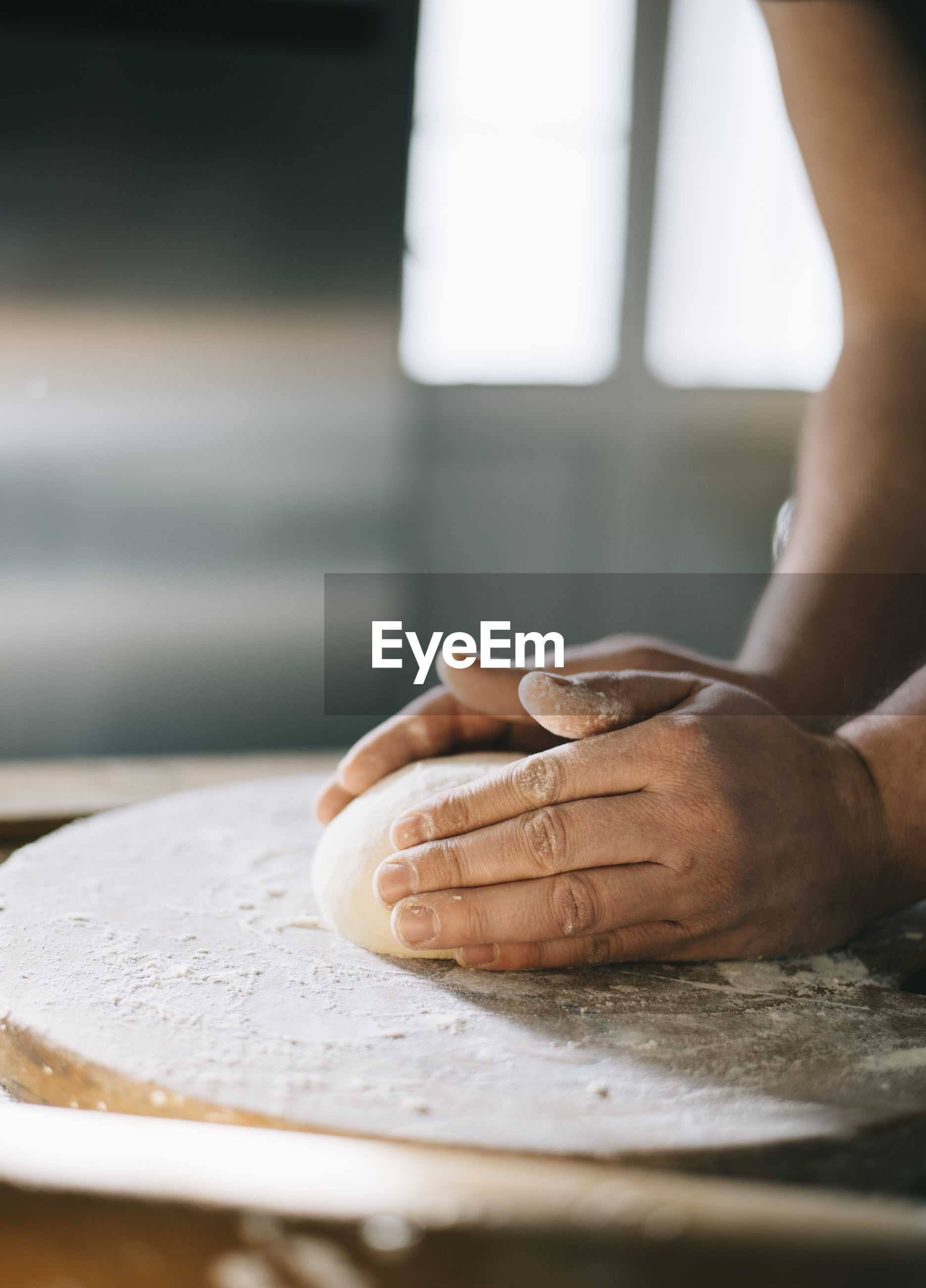 Cropped hand of person preparing food in kitchen