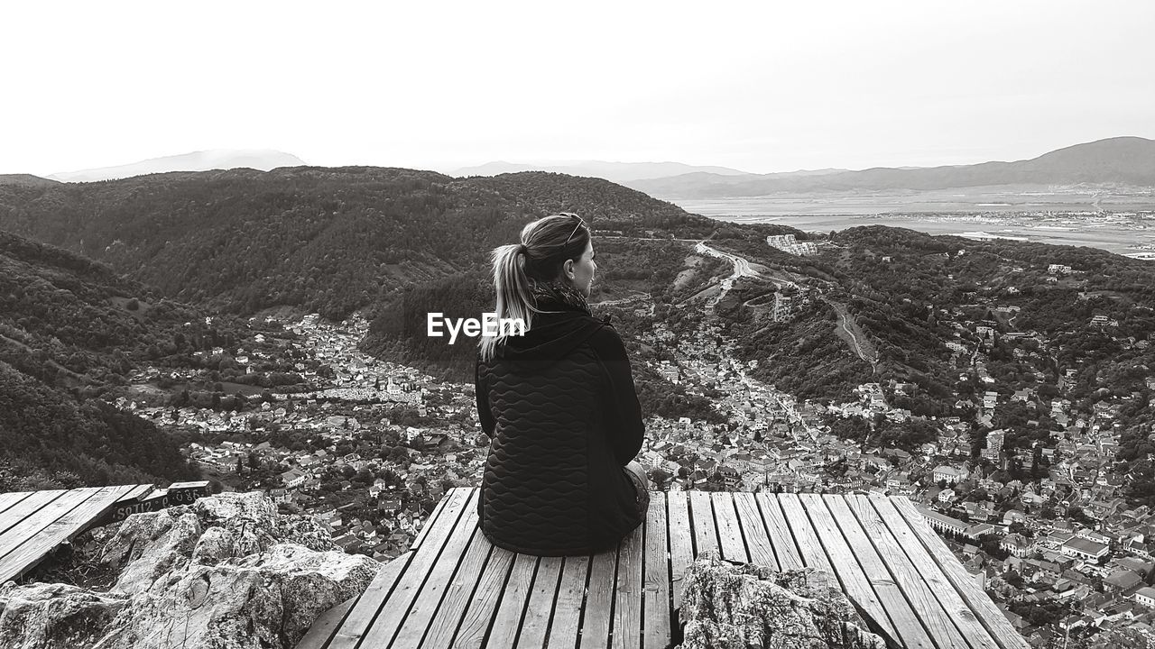 Rear View Of Mid Adult Woman Looking At Mountains While Sitting On Observation Point Against Clear Sky