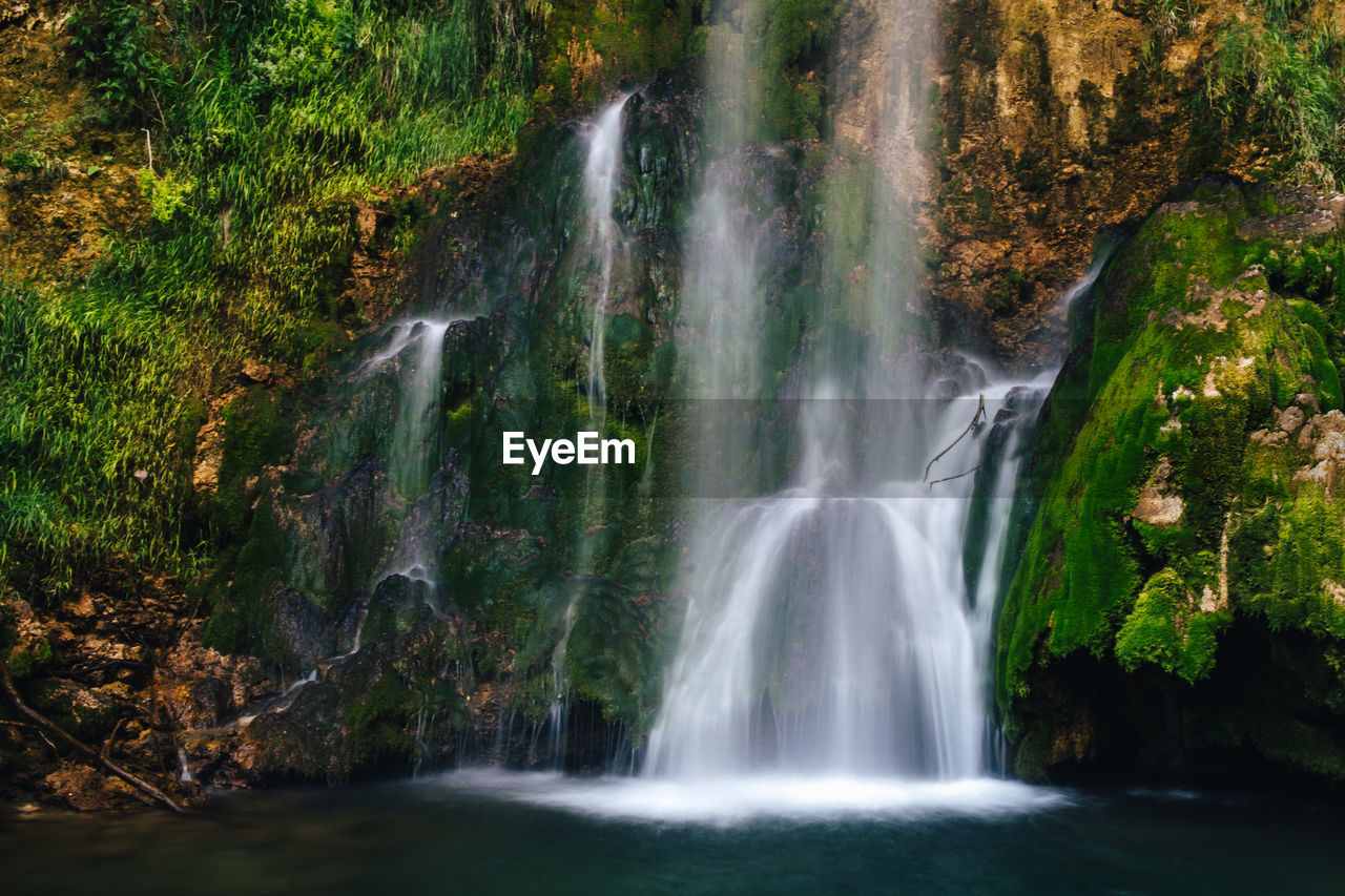 waterfall, scenics - nature, water, beauty in nature, long exposure, motion, flowing water, rock, land, forest, rock - object, environment, tree, blurred motion, solid, nature, no people, plant, moss, rainforest, flowing, power in nature, outdoors