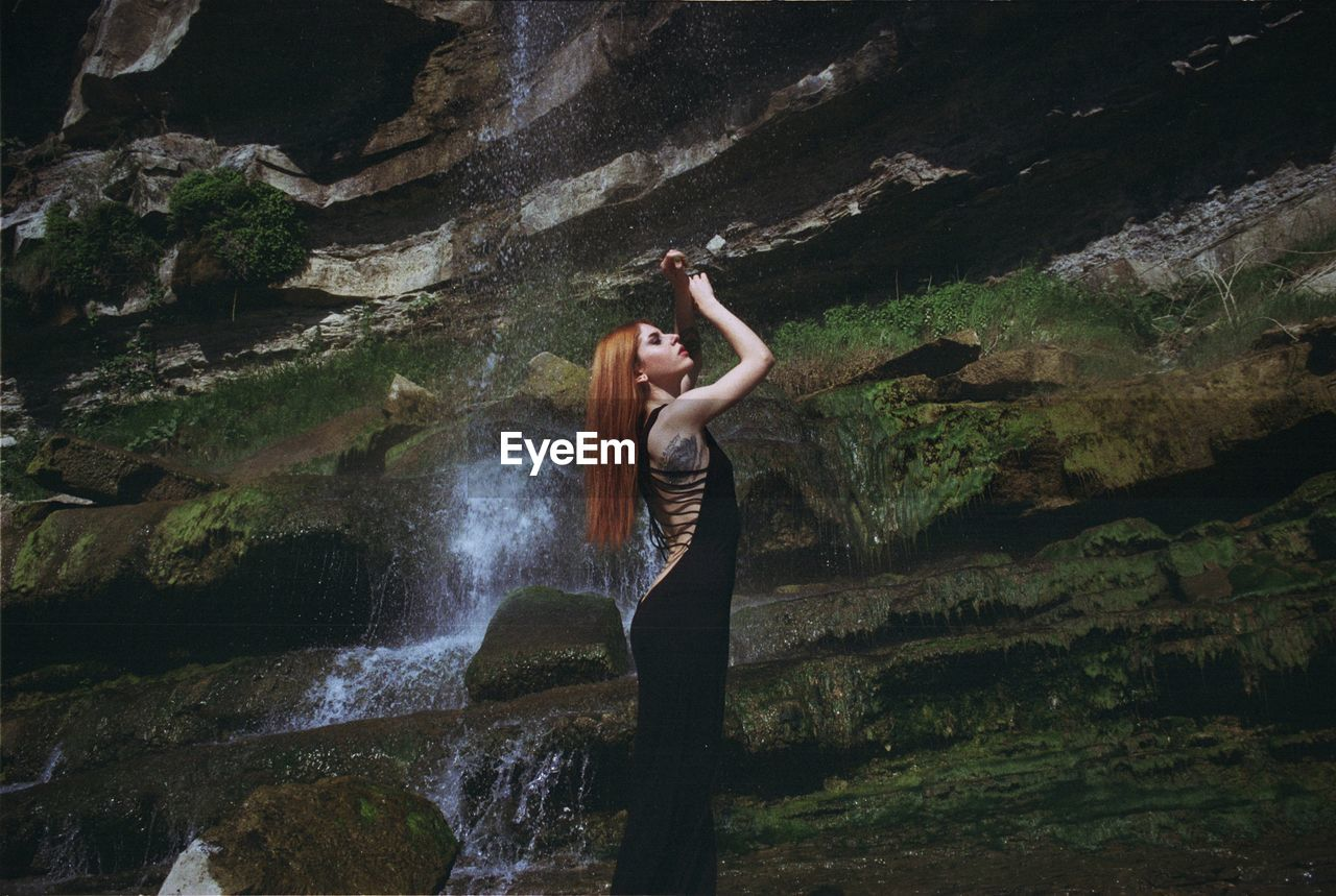 Side view of beautiful redhead woman standing against waterfall