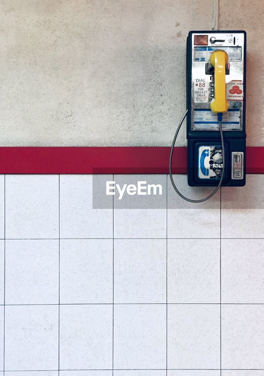 flooring, wall - building feature, technology, tile, telephone, connection, communication, no people, pay phone, tiled floor, indoors, telephone receiver, day, convenience, telecommunications equipment, wall, architecture, blue
