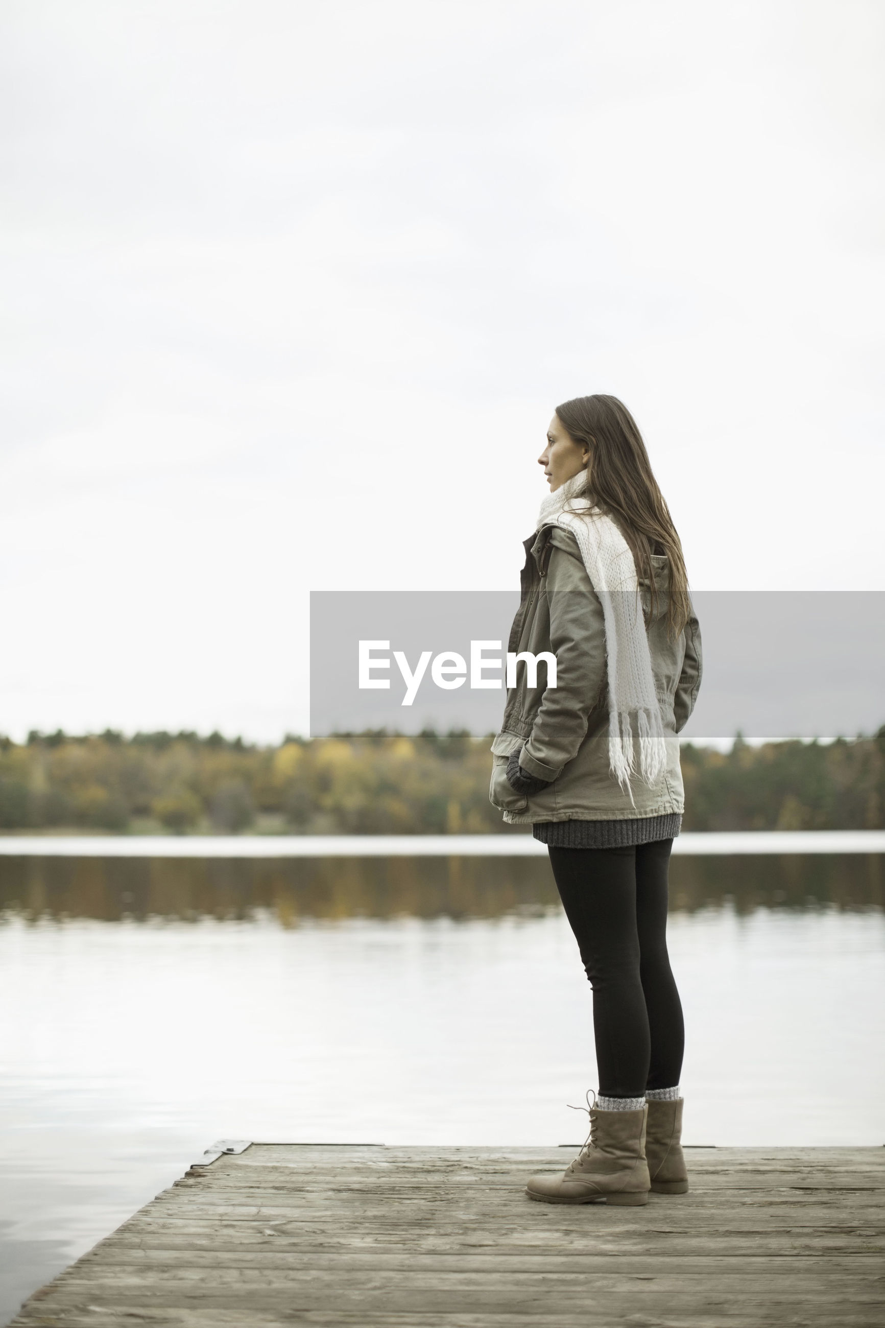 SIDE VIEW OF WOMAN STANDING AGAINST LAKE
