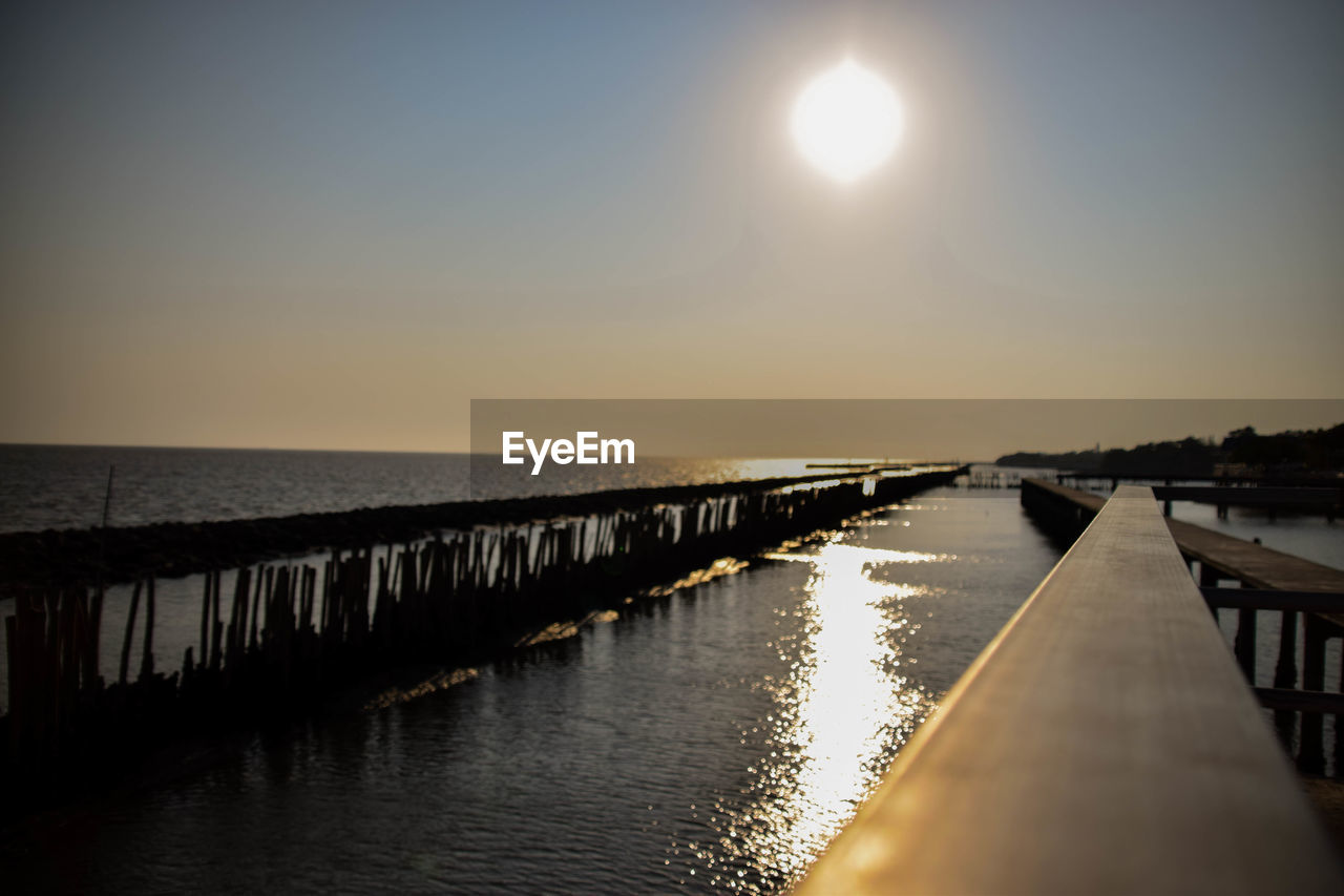 water, sky, scenics - nature, tranquility, tranquil scene, sea, horizon, reflection, sun, beauty in nature, horizon over water, nature, sunset, sunlight, no people, clear sky, pier, outdoors, idyllic, diminishing perspective, bright