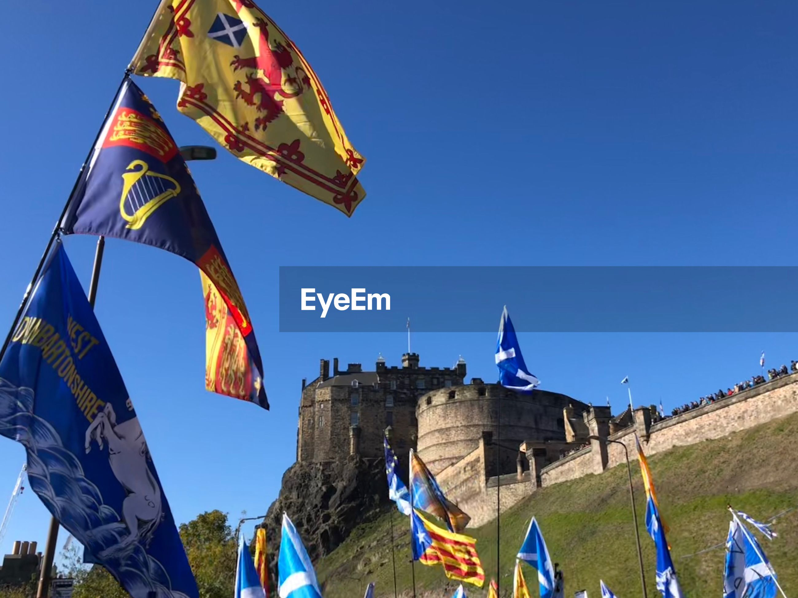 Low angle view of flags hanging against blue sky