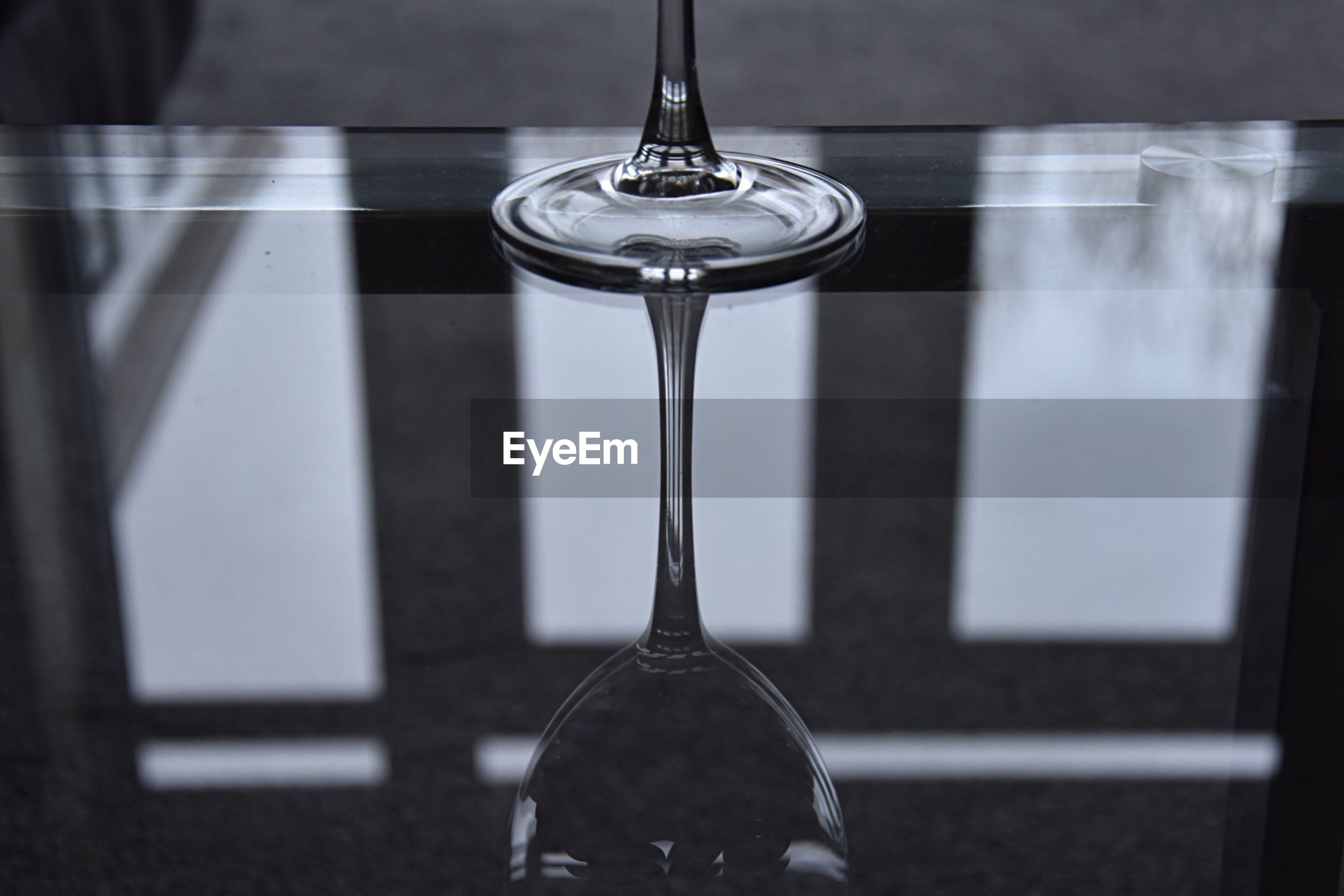 Close-up of a wine glass with reflections on a glass table