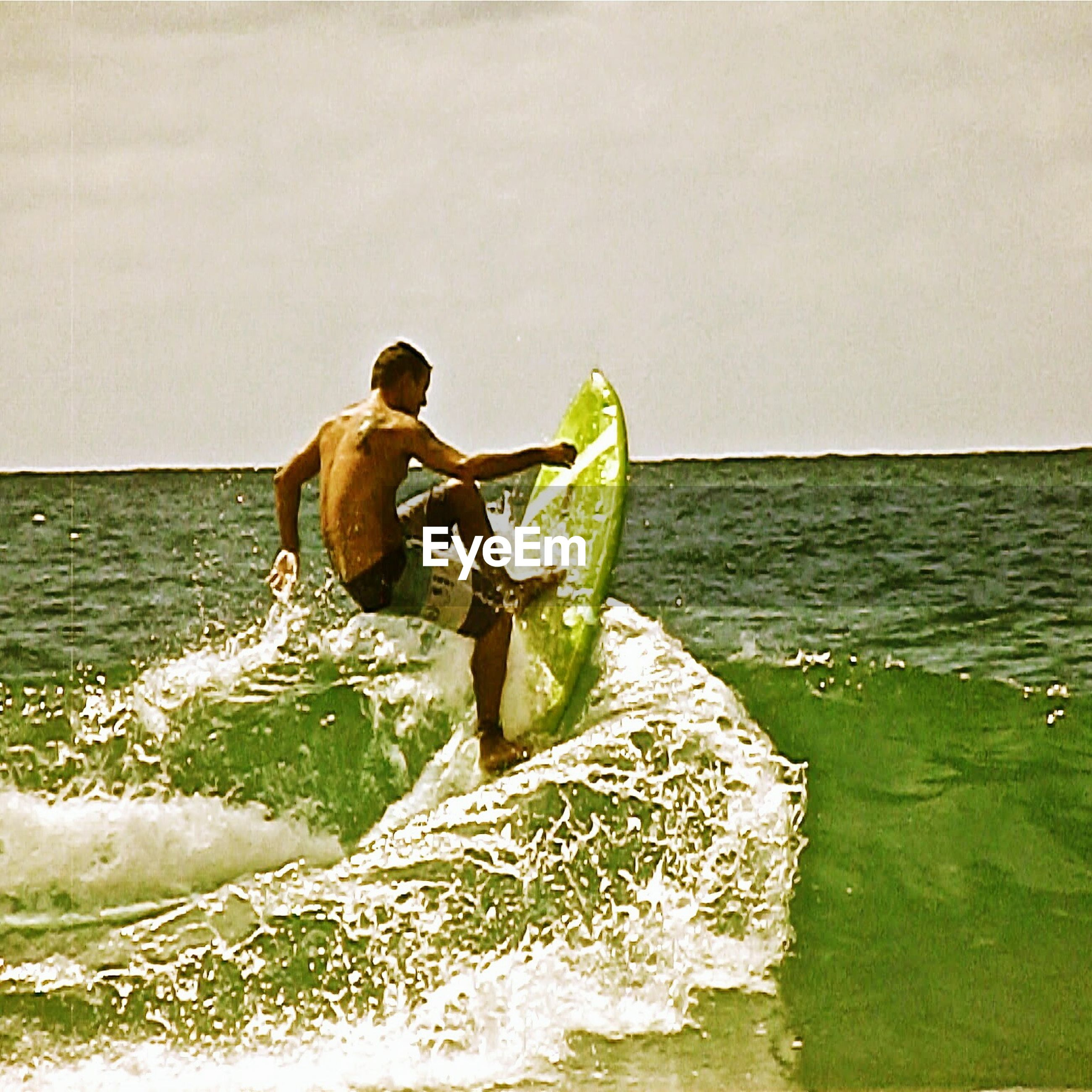 water, full length, lifestyles, sea, leisure activity, horizon over water, casual clothing, clear sky, rear view, young adult, copy space, standing, nature, men, person, beauty in nature, side view, holding